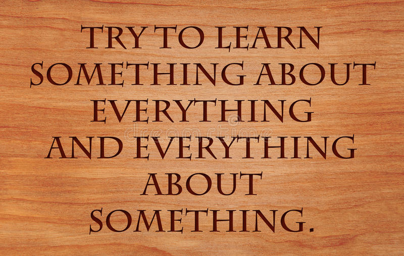 Try to learn something about everything. And everything about something - quote by Thomas Henry Huxley on wooden red oak background stock images