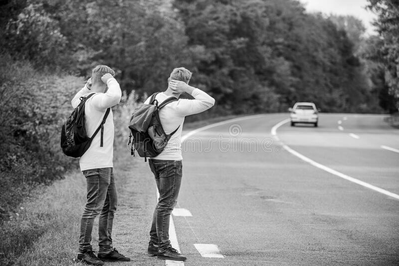 Try to stop some car. Travel and transport concept. Twins men at edge of road nature background. Reason people pick up. Hitchhikers. Missed their bus. Need help stock photography