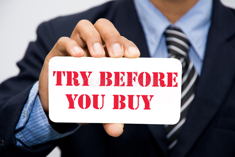 TRY BEFORE YOU BUY. Businessman hand holding TRY BEFORE YOU BUY concept royalty free stock image