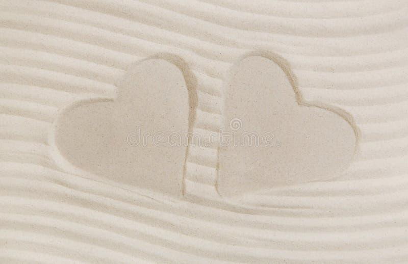 Tryck för två hjärtor i sanden Sommarstrand och semesterbegrepp royaltyfria foton