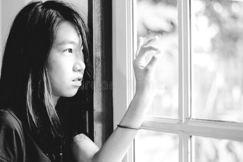Tryck ned och den hopplösa flickan med frånvarande sinnat se utanför royaltyfri foto