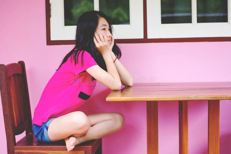 Tryck ned och den hopplösa flickan som sitter utomhus- frånvarande sinnat arkivfoto