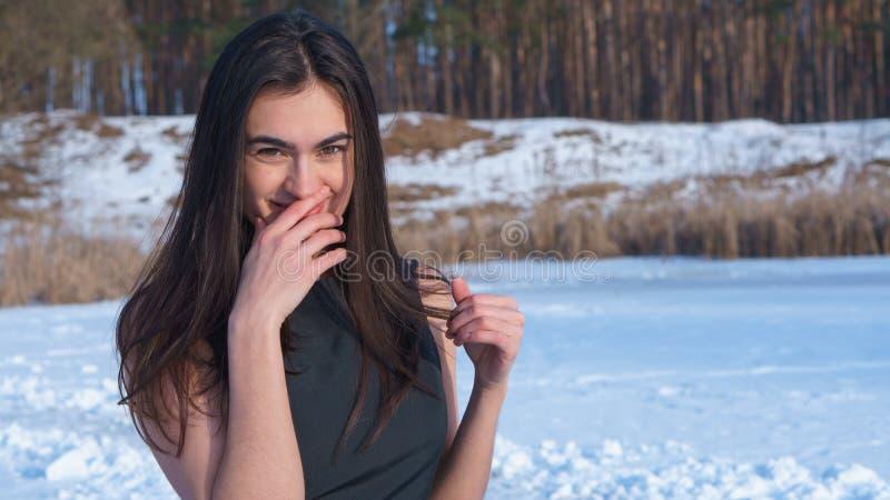 Trycker på den attraktiva le unga brunettflickan för ståenden hennes framsida med handen på en snöig landskapbakgrund royaltyfri fotografi