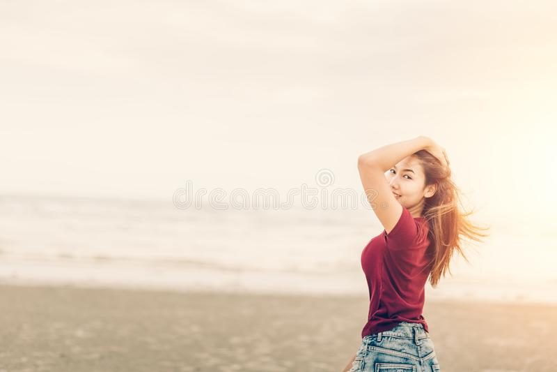 Trycker på kvinnor hennes hår, och hon är leendet på stranden kvinnor stående och solnedgång, soluppgång royaltyfria bilder