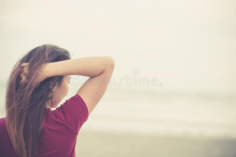 Trycker på kvinnor hennes hår på stranden kvinnor stående och solnedgång, soluppgång royaltyfri fotografi