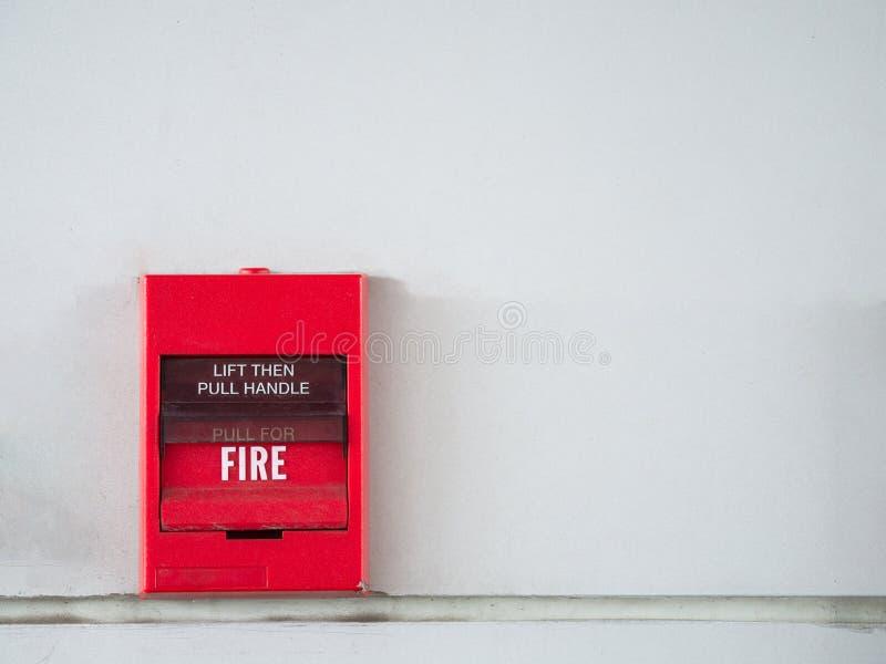 Tryckknappströmbrytaren, brandlarmet på den gråa väggen för larm och säkerhetssystemet med brandsläckaren port arkivbild
