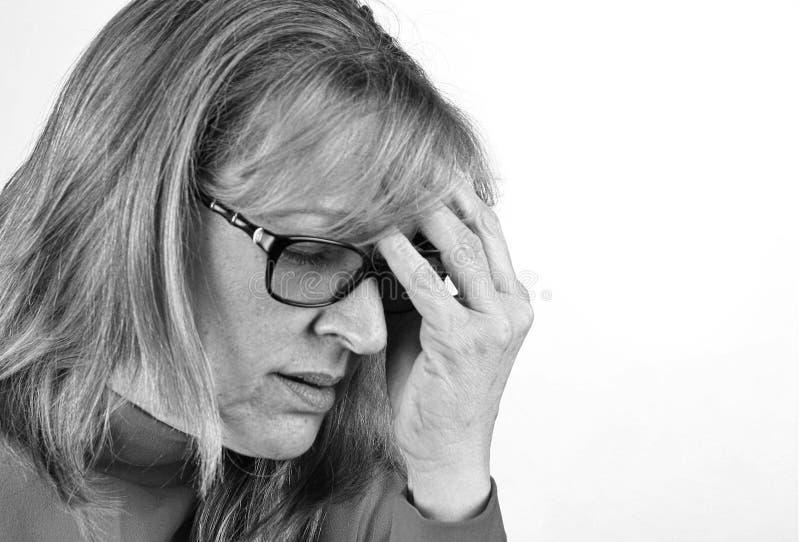Tryckt ned angelägen kvinna med handen på huvudet Svartvitt som isoleras med kopieringsutrymme arkivfoto