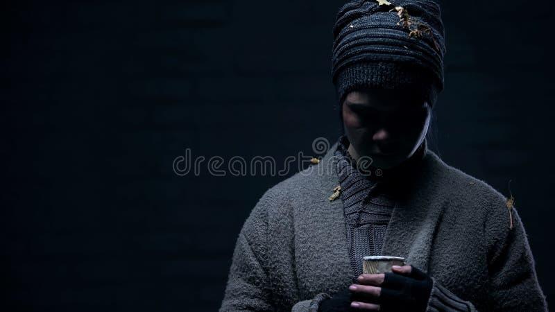 Tryckt ned hemlös med papperskoppen på svart bakgrund, bedrövligt liv, armod arkivbilder