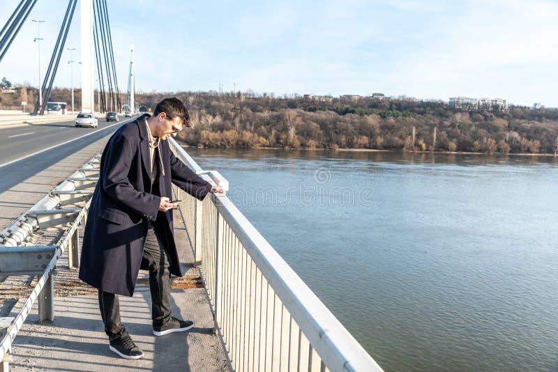 Tryckt ned och angeläget mananseende på bron med självmords- tankar som svikas i folk som ner ser för att hoppa i vattnet a royaltyfri fotografi