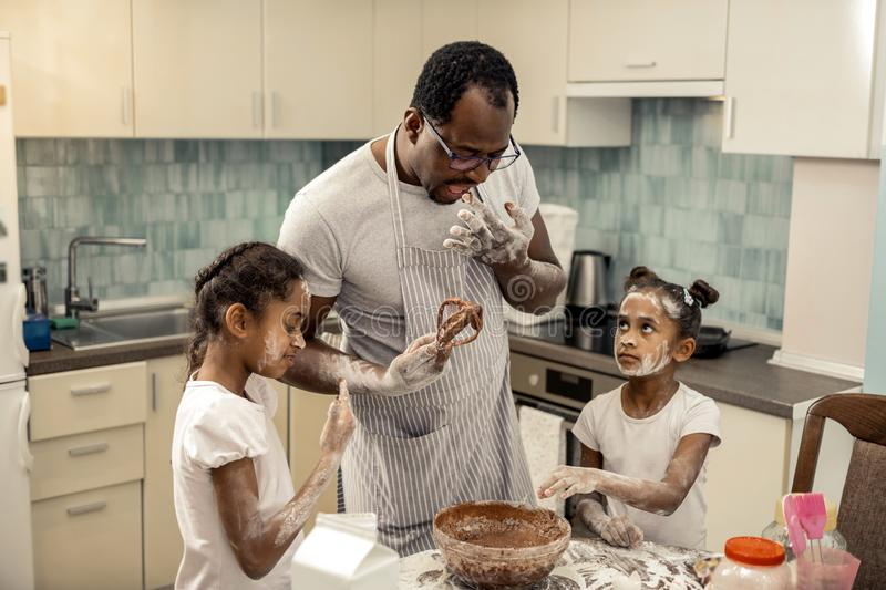 Father trying chocolate mousse while cooking with daughters. Trying chocolate mousse. Father wearing glasses trying chocolate mousse while cooking with daughters stock photo