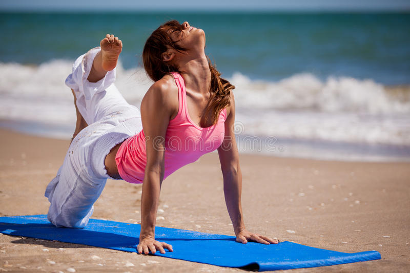 Trying a new yoga pose at the beach. Gorgeous Hispanic woman trying a new yoga pose in the beach royalty free stock images