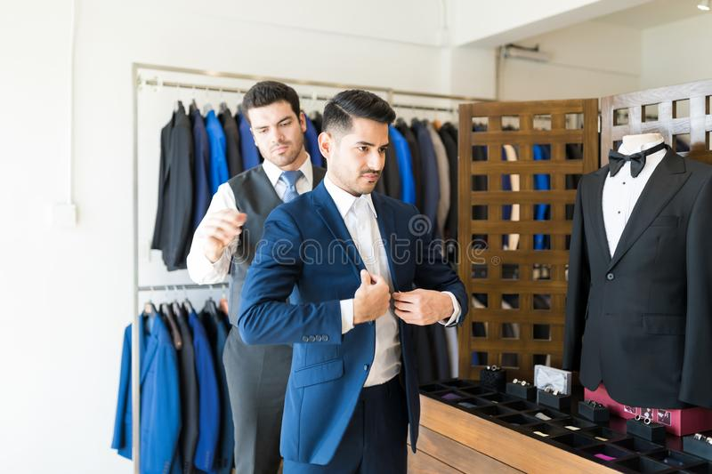 Trying Perfect Fit Blazer At Tailor Shop. Young male clerk assisting customer trying on suit at rental store stock photo