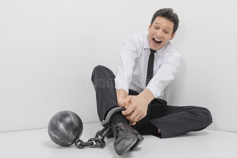 Trying to get freedom. Shocked businessman sitting on the floor royalty free stock photography