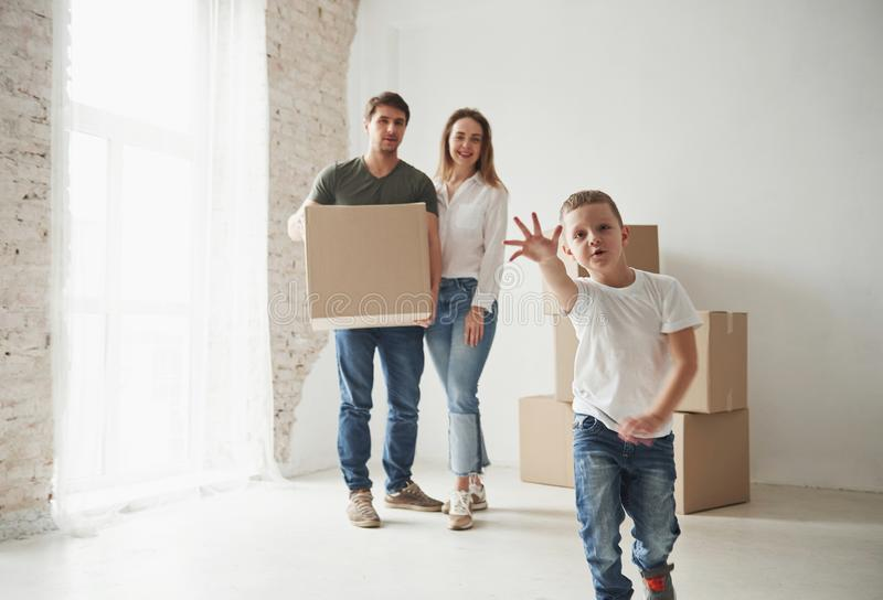 Trying to reach the camera. Playful mood from the kid. Family have removal into new house. Unpacking moving boxes stock photos