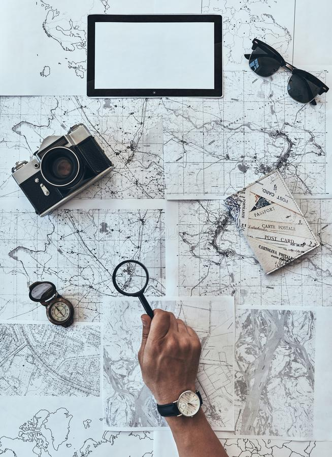Trying to see every detail. Close up top view of man using magnifying glass on map with sunglasses, photo camera, compass, passport lying around stock photography