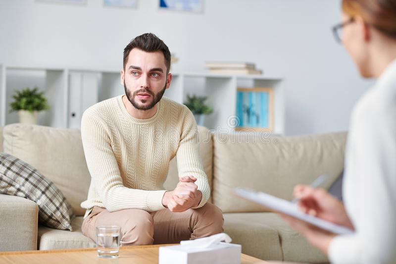 Trying to solve problem. Distracted young men visiting his psychologist to speak out all problems and try to solve them stock photo