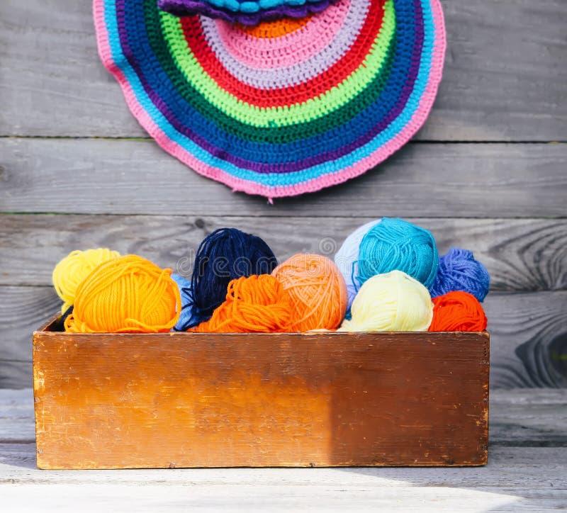 Trykotowe kolorowe pasiaste maty i piłki jaskrawa woolen przędza w drewnianym pudełku na starym drewnie izolują tło obraz royalty free