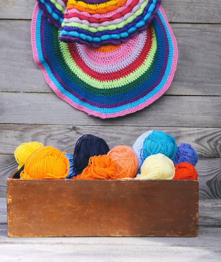 Trykotowe kolorowe pasiaste maty i piłki jaskrawa woolen przędza w drewnianym pudełku na starym drewnie izolują tło zdjęcie royalty free