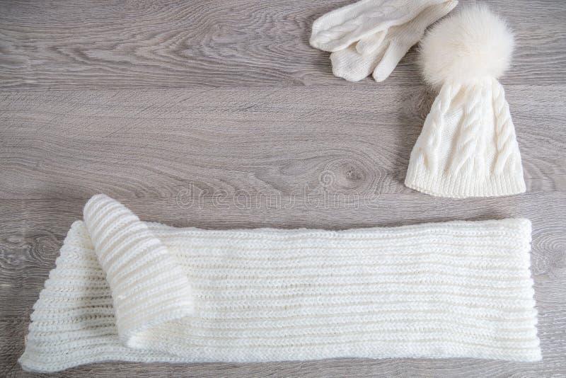 Trykotowy zimnej pogody akcesorium na stole Biały kapelusz, szalik mrówki rękawiczki siwieje drewnianego tło Odgórny widok kosmos obraz stock