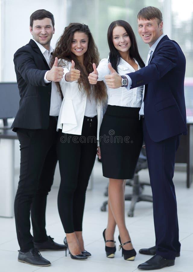 Tryumfalne biznes drużyny mienia aprobaty zdjęcie stock