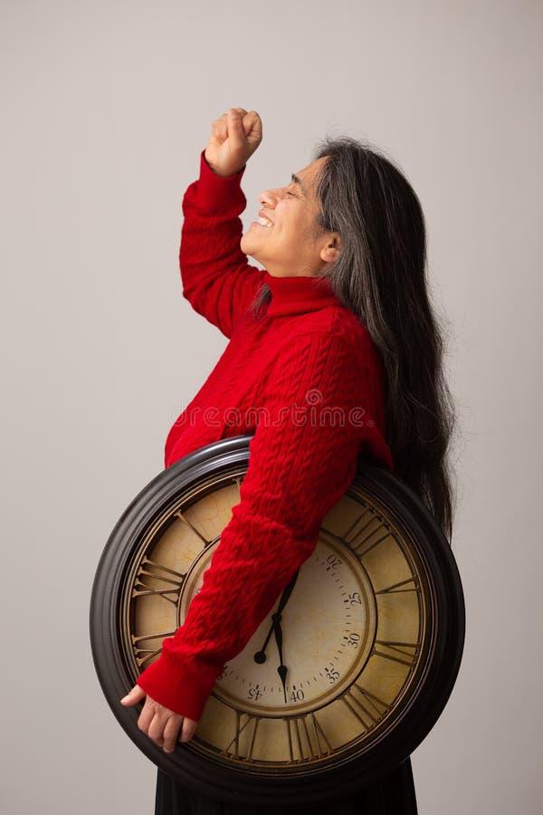 Tryumfalny Latynoski kobiety mienia zegar Podnosi pięść W powietrze obraz royalty free