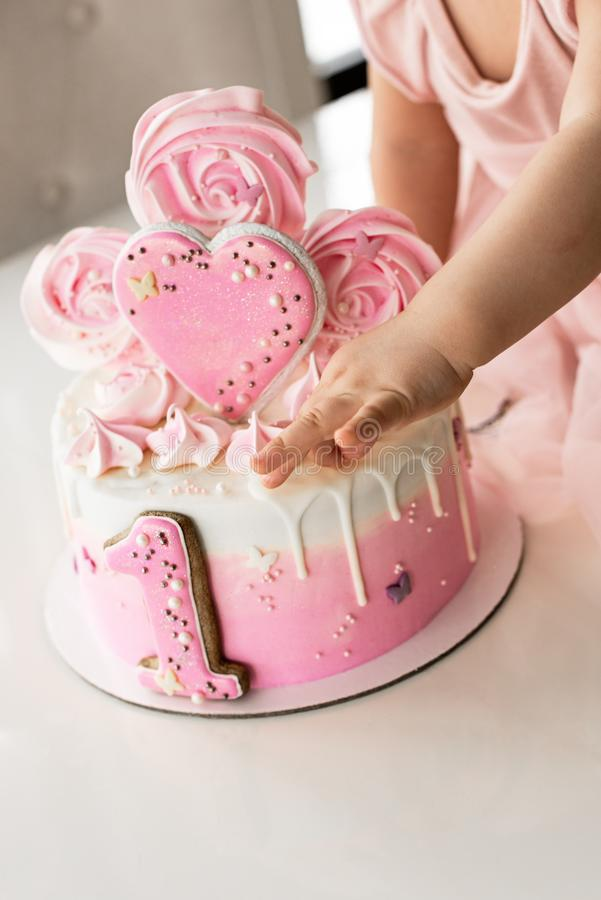 Trzask menchie zasychaj? przy ?wi?towaniem pierwszy urodziny dziewczyna, rujnuj?cy g?bka tort, ?amaj?cy marshmallow, dziecko wr?c zdjęcie stock