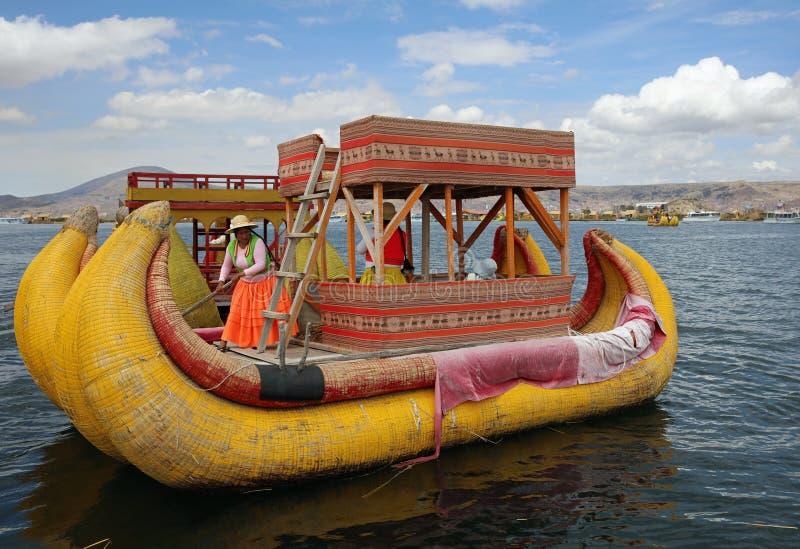 Trzcinowa łódź z rodzimymi ludźmi przy Uros Spławowymi wyspami w Jeziornym Titicaca Peru fotografia stock