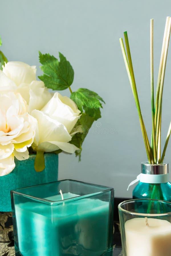 Trzcinowy dyfuzor z drewnianymi kijami w turkusowym szklanej butelki świeczek bukiecie kwiaty na stołowych szarość izoluje tło Ar obrazy stock