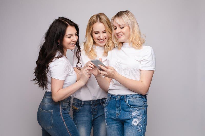 Trzech przyjaciół w białej koszuli i dżinsach patrzących na telefon obraz royalty free