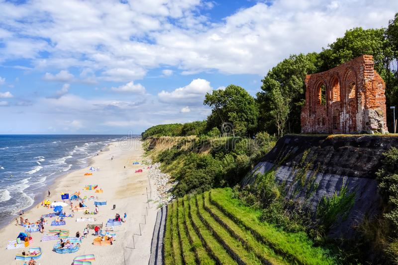 Single wall of ruined church on the edge of cliff, people on the sandy beach below stock photos