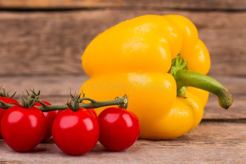 Trzon czerwoni błyszczący pomidory i żółty dzwonkowy pieprz zdjęcia stock