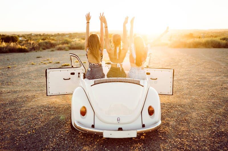 Trzy ładnej młodej kobiety jedzie na wycieczce samochodowej na pięknym summe zdjęcia stock