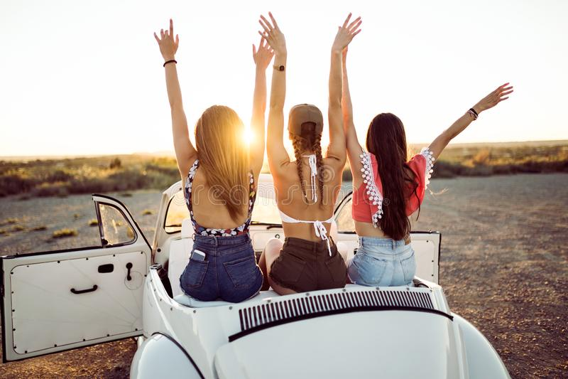 Trzy ładnej młodej kobiety jedzie na wycieczce samochodowej na pięknym summe obrazy royalty free