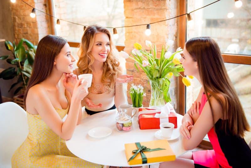 Trzy ładny, powabne dziewczyny siedzi w kawiarni w eleganckich sukniach, obraz stock