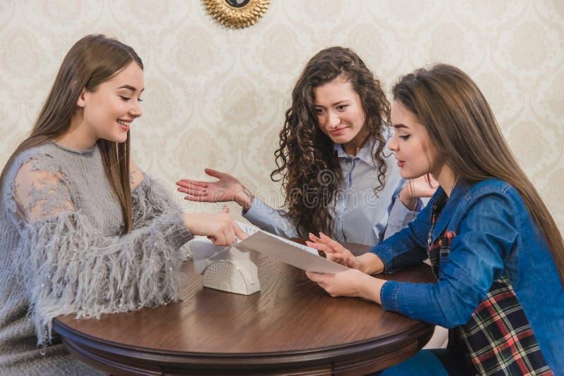 Trzy ślicznej dziewczyny siedzą w sklepie z kawą i wybierają rozkazy W tym samym czasie gawędzić uśmiech Trzy brunetki z obraz royalty free