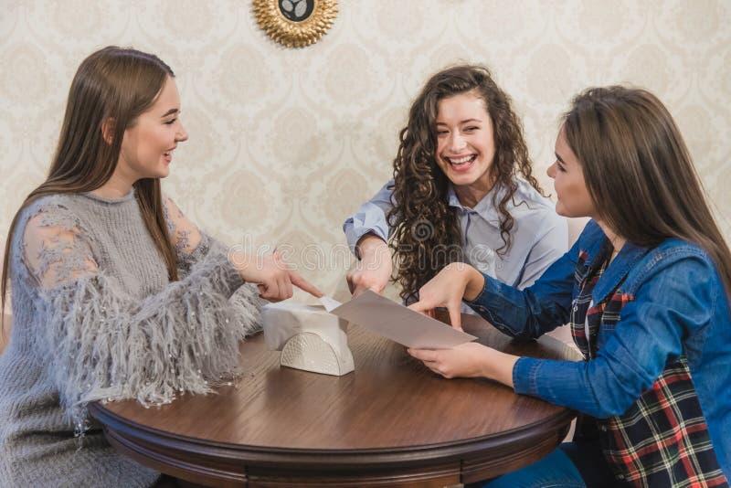 Trzy ślicznej dziewczyny siedzą w sklepie z kawą i wybierają rozkazy W tym samym czasie gawędzić uśmiech Trzy brunetki z fotografia stock