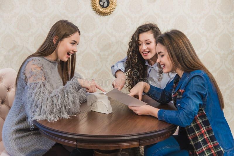 Trzy ślicznej dziewczyny siedzą w sklepie z kawą i wybierają rozkazy W tym samym czasie gawędzić uśmiech Trzy brunetki z zdjęcie stock