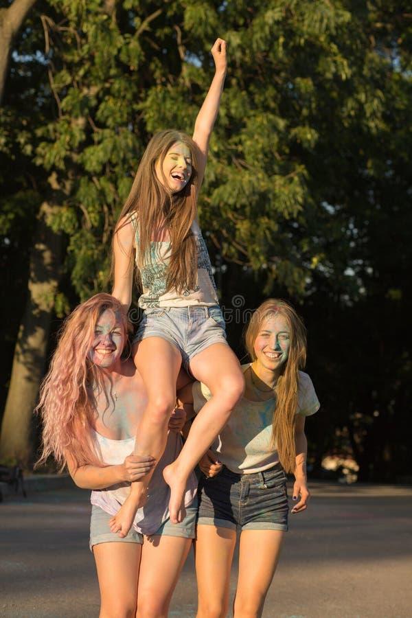 Trzy śmiesznego młoda kobieta przyjaciela ma zabawę przy Holi festiwalem obrazy stock