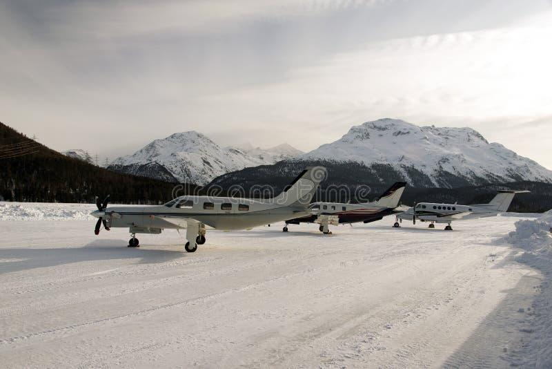 Trzy śmigieł typ intymny strumień i samoloty w śniegu zakrywał lotnisko w alps Switzerland w zimie obrazy stock