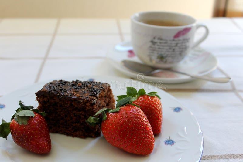 Trzy świeżej czerwonej truskawki wokoło czekoladowego torta i filiżanki kawy przy tłem wyśmienicie i smakowitego fotografia stock
