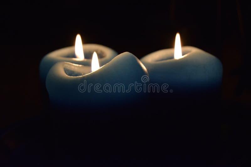 Trzy świeczki światła w ciemności obraz royalty free