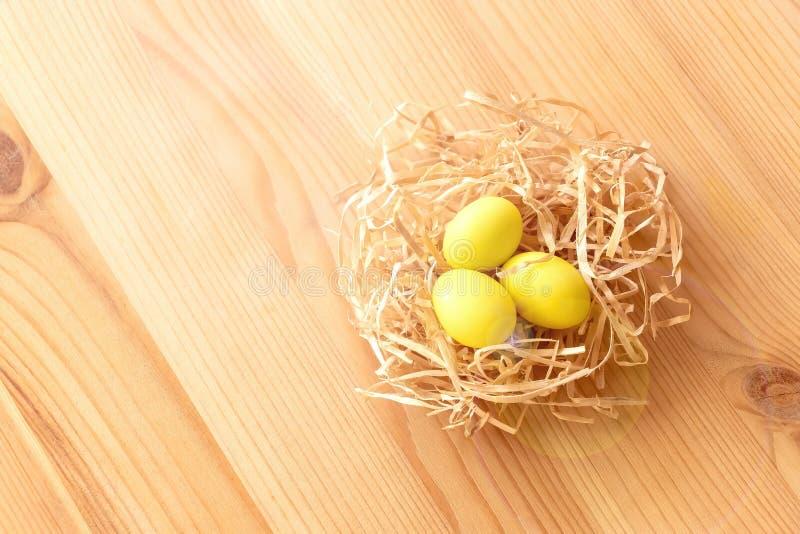 Trzy żółtego jajka w gniazdeczku na lekkim drewnianym tle Wielkanoc świętuje pojęcie fotografia stock