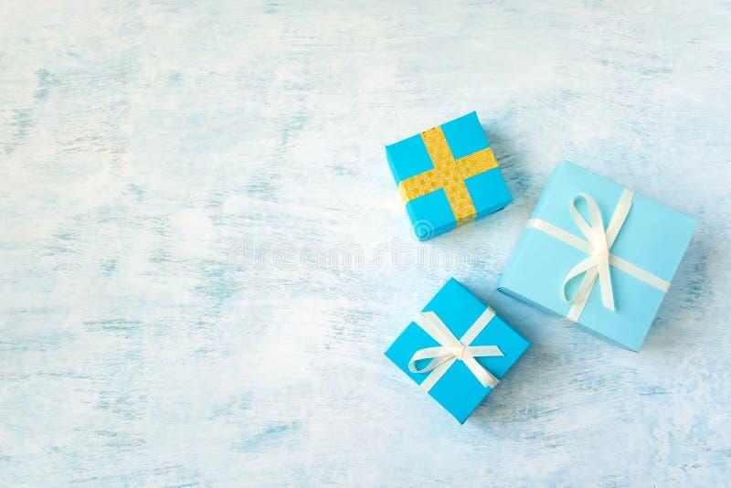 trzy Żółty, błękitny prezenta pudełko z białym faborkiem i łęk na ligh fotografia royalty free