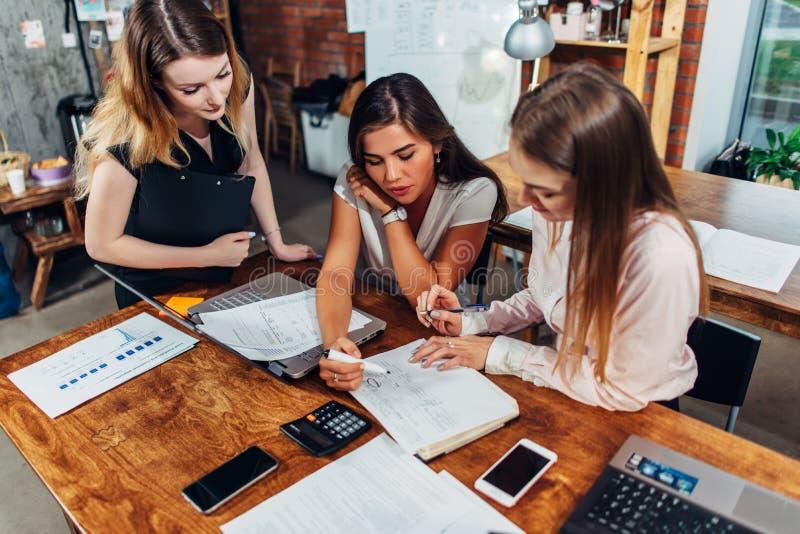 Trzy żeńskiego ekonomisty sprawdza dokumentację analizuje dokumenty siedzi przy biurkiem w nowożytnym biurze obraz stock