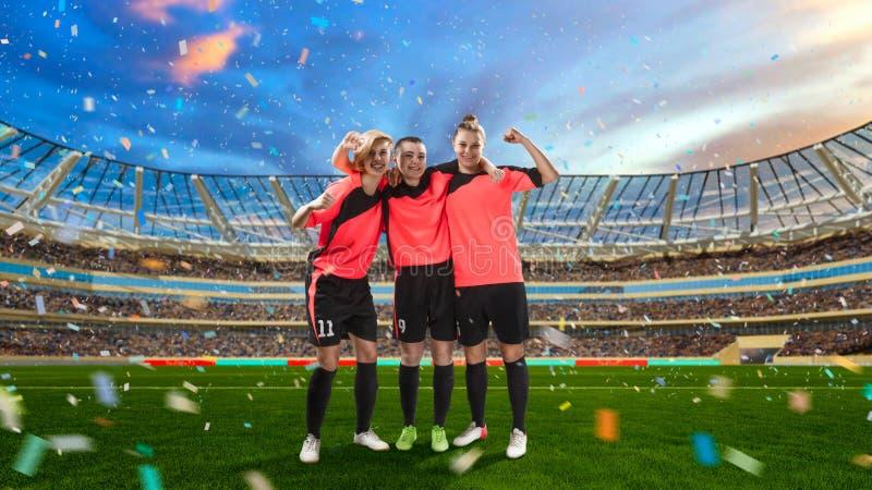 Trzy żeńskiego gracza piłki nożnej świętuje zwycięstwo na piłce nożnej segregującej fotografia royalty free