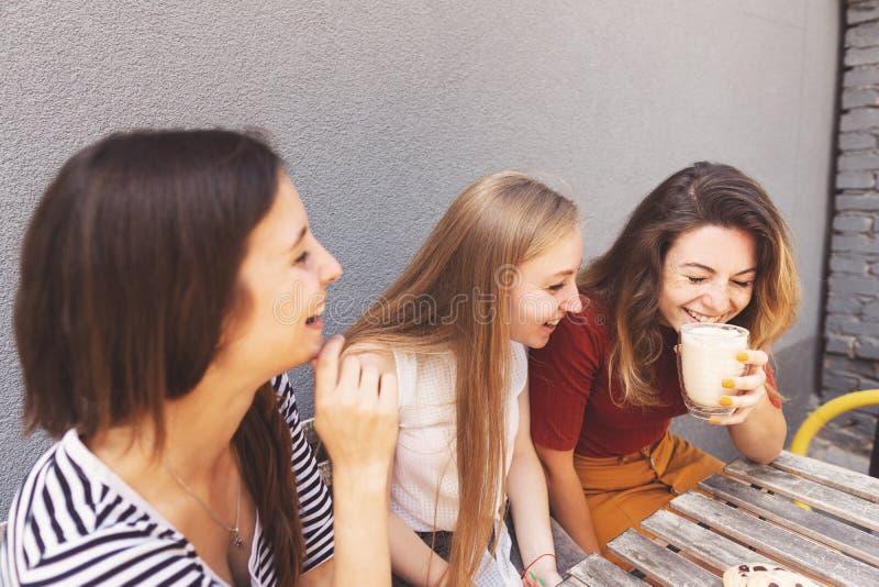 Trzy żeńskiego przyjaciela ma wielkiego czas przy kawiarnią zdjęcie royalty free