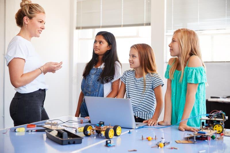 Trzy Żeńskiego ucznia Z nauczyciela budynku robota pojazdem Wewnątrz Po Szkolnej Komputerowej cyfrowanie klasy zdjęcie royalty free