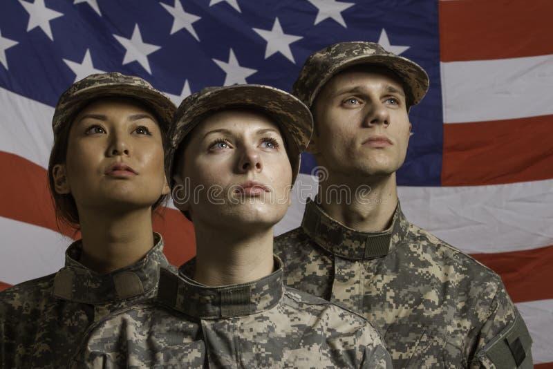 Trzy żołnierza pozującego przed flaga amerykańską, horyzontalną fotografia royalty free