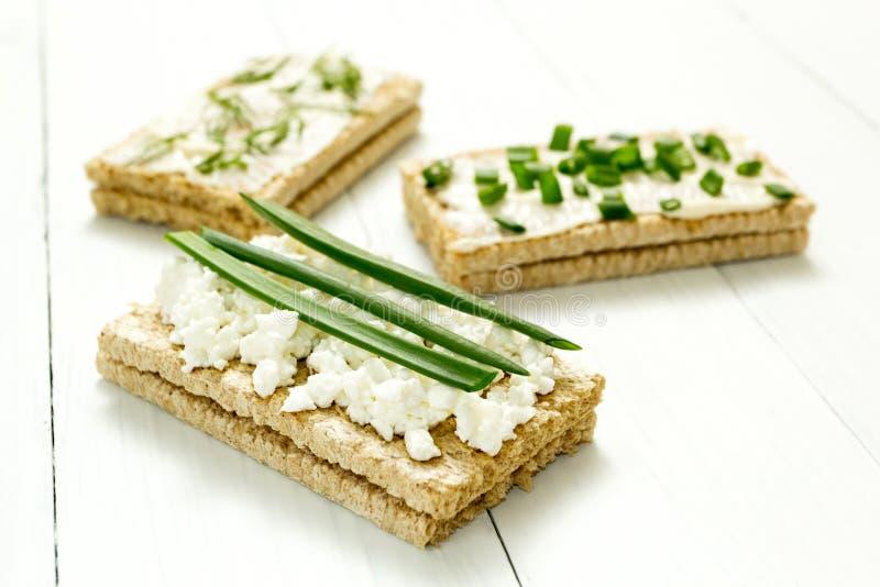 Trzy żywienioniowej przekąski z chałupa serem i zielenie na białym drewnianym stole, zdrowy jedzenie zdjęcia stock