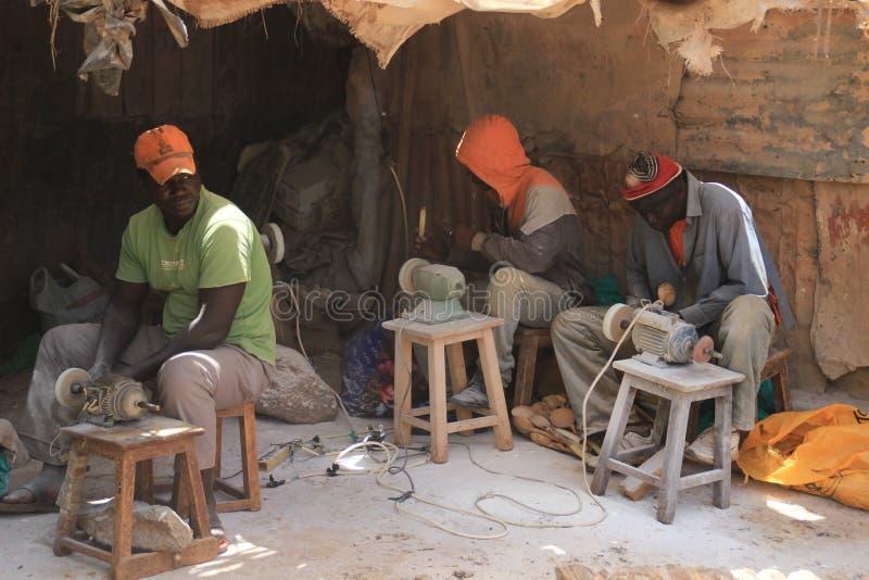 Trzy Afrykańskiego młodego człowieka pracuje przy pamiątkarską fabryką w biednym okręgu Nairobia - Kibera siedzi na krzesłach i w zdjęcie stock